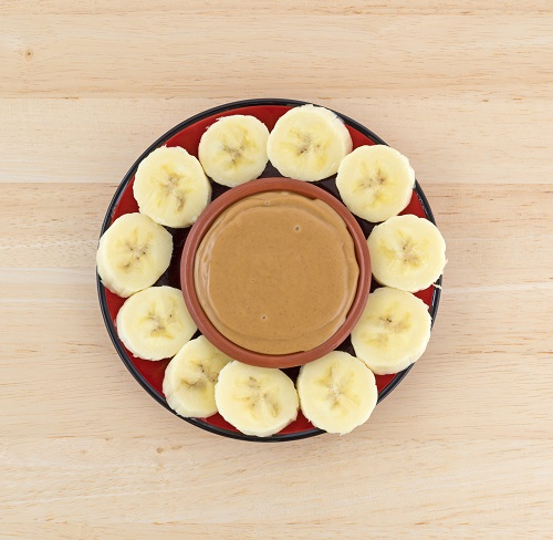 Top view of sliced bananas on a red plate in a circle around a bowl of peanut butter on a wood table.